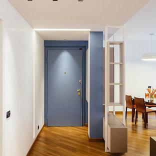 Idee per un corridoio minimal con pavimento in legno massello medio e una porta blu