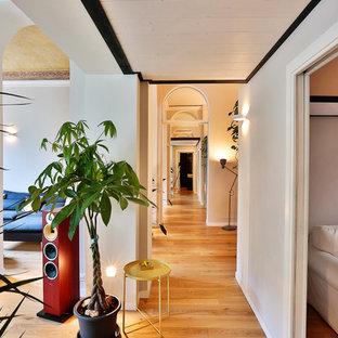 Immagine di un grande ingresso o corridoio design con pareti bianche, pavimento in legno massello medio e pavimento marrone