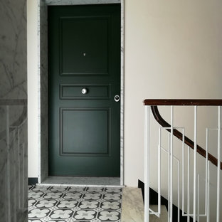 Small elegant concrete floor and gray floor entryway photo in Other with beige walls and a green front door