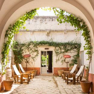 Ispirazione per un ampio corridoio mediterraneo con pareti bianche, una porta a due ante, una porta bianca e pavimento beige