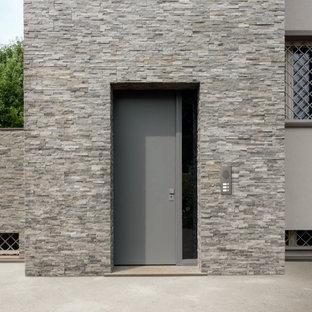 Exempel på en modern ingång och ytterdörr, med en enkeldörr och en grå dörr