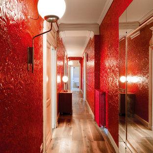 Foto de recibidores y pasillos contemporáneos con paredes rojas y suelo de madera en tonos medios
