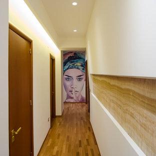 Idéer för en liten modern hall, med vita väggar och mellanmörkt trägolv
