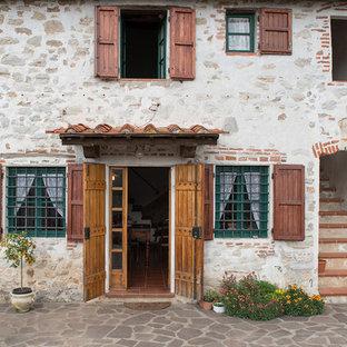 Ejemplo de entrada mediterránea con puerta doble y puerta de madera clara