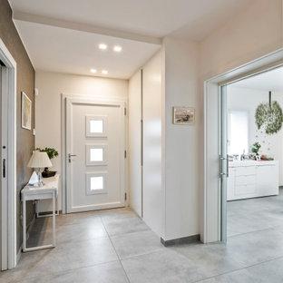 Foto på en mellanstor funkis foajé, med grå väggar, klinkergolv i porslin, en enkeldörr, en vit dörr och grått golv