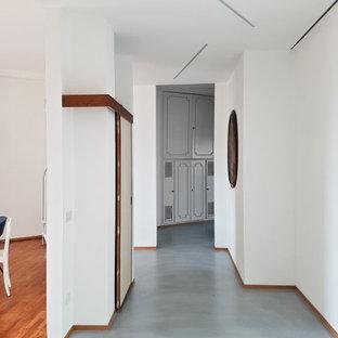 Foto på en funkis hall, med vita väggar och turkost golv