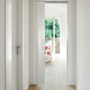 Ispirazione per un piccolo ingresso o corridoio design con pareti bianche, parquet chiaro e pavimento beige