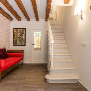 ヴェネツィアの片開きドア地中海スタイルのおしゃれな玄関ロビー (ピンクの壁、淡色無垢フローリング、白いドア) の写真