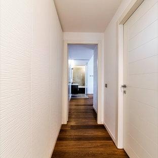Esempio di un ingresso o corridoio contemporaneo di medie dimensioni con pareti bianche, parquet chiaro e pavimento marrone