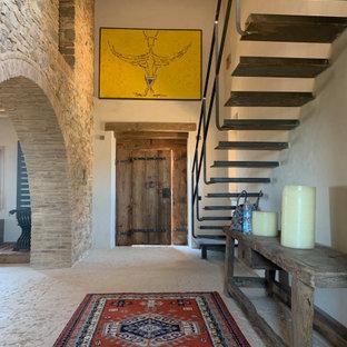 Medelhavsstil inredning av en mycket stor hall, med beige väggar, en enkeldörr, mellanmörk trädörr, beiget golv och kalkstensgolv