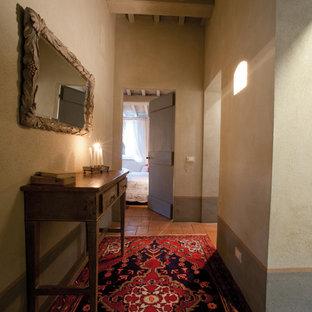 Inspiration pour un petit couloir rustique avec un mur beige et un sol en brique.