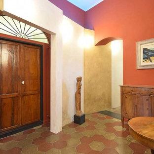 Idee per un grande ingresso o corridoio eclettico con pareti rosse, pavimento in terracotta e pavimento multicolore