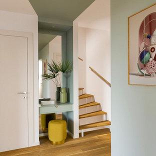 Idee per un piccolo ingresso design con pareti verdi, parquet chiaro, una porta a due ante e una porta bianca