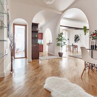 Esempio di un ingresso minimal con pareti bianche, pavimento in legno massello medio e pavimento marrone