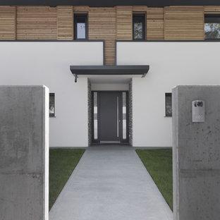 Immagine di una porta d'ingresso design di medie dimensioni con pareti bianche, una porta singola e una porta grigia