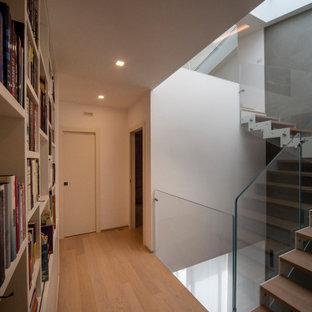 Immagine di un ingresso o corridoio contemporaneo di medie dimensioni con pareti bianche, parquet chiaro e pavimento marrone