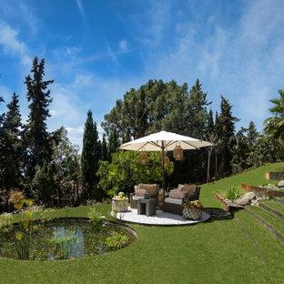 Diseño de jardín tropical, en ladera, con estanque