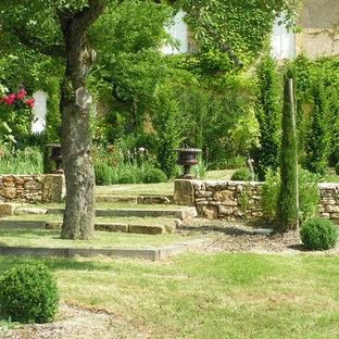 Cette image montre un grand jardin à la française traditionnel l'été avec une exposition ombragée et des pavés en pierre naturelle.