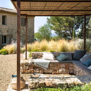 Immagine di una grande aiuola mediterranea esposta in pieno sole dietro casa con ghiaia