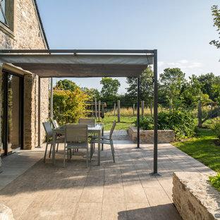 Inspiration pour un jardin arrière rustique de taille moyenne et l'été avec pierres et graviers, une exposition partiellement ombragée et des pavés en pierre naturelle.