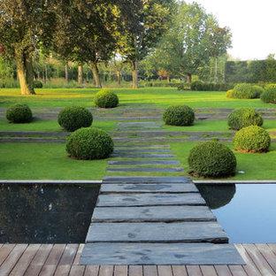 Cette photo montre un grand jardin moderne avec un point d'eau, une exposition ombragée, une pente, une colline ou un talus et des pavés en pierre naturelle.