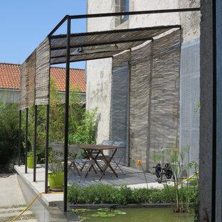 Стильный дизайн: солнечный участок и сад среднего размера на заднем дворе в стиле кантри с водопадом, хорошей освещенностью и мощением тротуарной плиткой - последний тренд