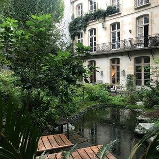 Idée de décoration pour un jardin avec une terrasse en bois ou composite arrière tradition avec un bassin.