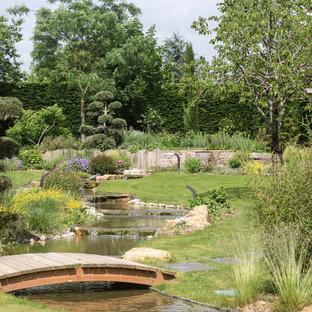 Cette image montre un grand jardin asiatique l'été avec un bassin, une exposition ensoleillée et des pavés en pierre naturelle.