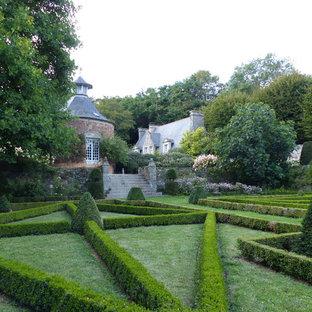 Réalisation d'un très grand jardin tradition l'été avec une exposition partiellement ombragée et une entrée ou une allée de jardin.