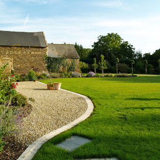 This is an example of a farmhouse backyard gravel lawn edging in Rennes.