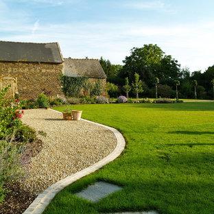 Aménagement d'un jardin arrière campagne avec du gravier et des bordures.
