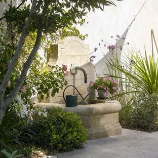 Réalisation d'un jardin méditerranéen avec un point d'eau et des pavés en pierre naturelle.