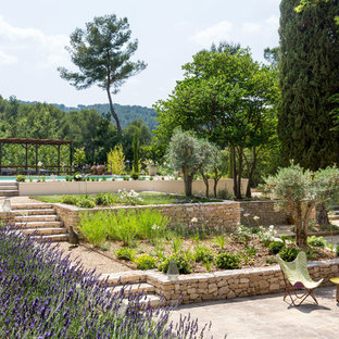 Inspiration pour un jardin à la française arrière méditerranéen avec un mur de soutènement et des pavés en pierre naturelle.