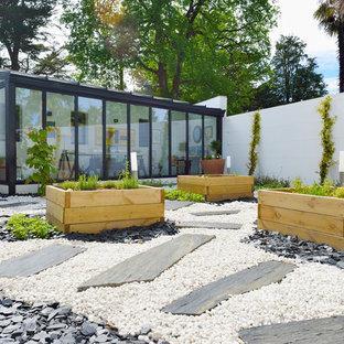 Inspiration pour un jardin arrière design de taille moyenne avec une exposition ensoleillée et des pavés en pierre naturelle.