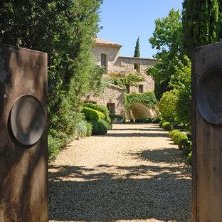 Exemple d'une grand allée carrossable avant méditerranéenne l'été avec une entrée ou une allée de jardin, du gravier et une exposition partiellement ombragée.