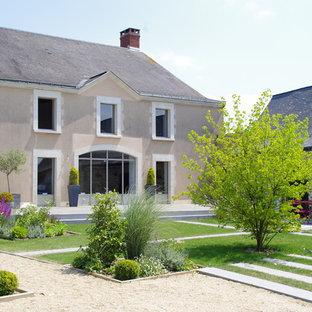 Cette image montre un grand jardin arrière design l'été avec une entrée ou une allée de jardin, une exposition ensoleillée et du gravier.