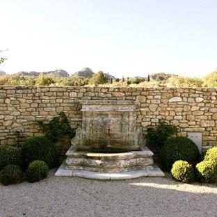 Idée de décoration pour un grand jardin arrière méditerranéen avec un point d'eau et du gravier.