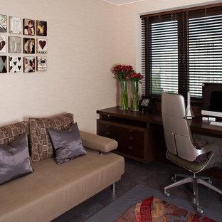 Idéer för mellanstora funkis hemmabibliotek, med beige väggar, korkgolv och ett inbyggt skrivbord