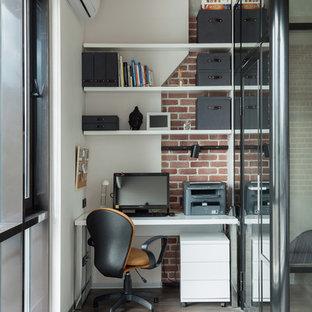 Idéer för små industriella hemmabibliotek, med ett fristående skrivbord, flerfärgade väggar och mellanmörkt trägolv