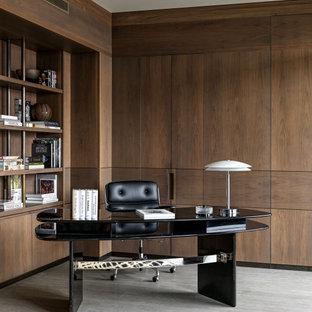 Стильный дизайн: большое рабочее место в современном стиле с коричневыми стенами, отдельно стоящим рабочим столом и серым полом - последний тренд