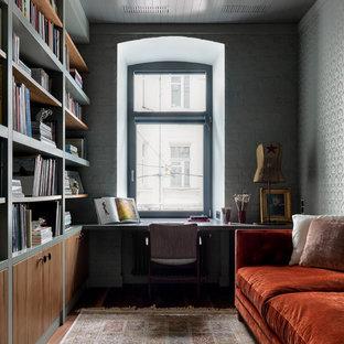 На фото: домашняя библиотека в современном стиле с серыми стенами, встроенным рабочим столом и темным паркетным полом без камина с