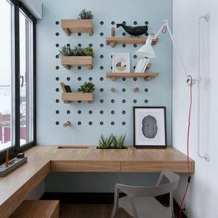 Пример оригинального дизайна: рабочее место в современном стиле с белыми стенами, паркетным полом среднего тона, встроенным рабочим столом и коричневым полом