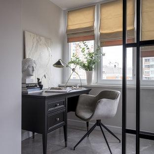 На фото: рабочее место среднего размера в стиле современная классика с серыми стенами, отдельно стоящим рабочим столом и серым полом