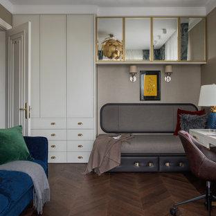Пример оригинального дизайна: большое рабочее место в современном стиле с бежевыми стенами, темным паркетным полом, коричневым полом и отдельно стоящим рабочим столом без камина