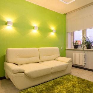 Foto di uno studio design di medie dimensioni con libreria, pareti verdi, pavimento in laminato, scrivania autoportante e pavimento beige