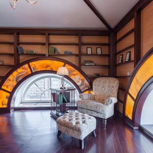 Foto di uno studio chic di medie dimensioni con libreria, pareti marroni, parquet scuro, scrivania autoportante e pavimento marrone