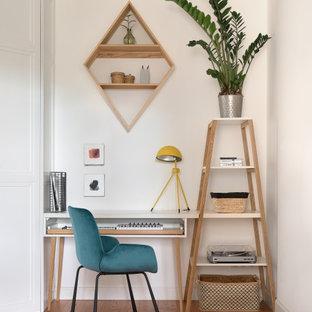 На фото: кабинет в скандинавском стиле с белыми стенами, паркетным полом среднего тона, отдельно стоящим рабочим столом и коричневым полом с