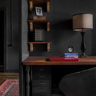 Foto di un ufficio industriale di medie dimensioni con pareti nere, pavimento in laminato, scrivania autoportante e pavimento marrone