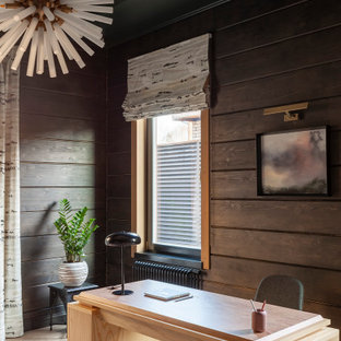 Example of a mountain style freestanding desk tray ceiling and wood wall home office design in Moscow with black walls