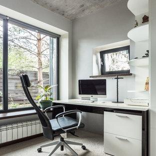 Стильный дизайн: рабочее место в стиле лофт с серыми стенами, ковровым покрытием, отдельно стоящим рабочим столом и бежевым полом - последний тренд